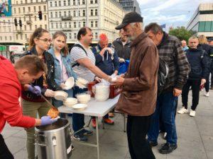Zdjęcie przedstawia rozdanie posiłków na Dworcu Centralnym przez Wolontariuszy i członków Fundacji Daj Herbatę. Osoby bezdomne dostają ciepły posiłek i kanapkę.